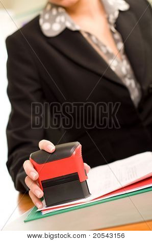 Woman's hand with stamping documents
