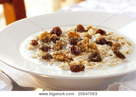 Bowl of oatmeal topped with raisins, walnuts and brown sugar.  Healthy eating.