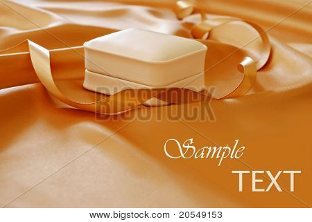 Elegant jewelry gift box on shimmery gold satin with matching ribbon.  Macro with shallow dof and copy space.