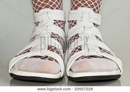 Feet In White Sandals.
