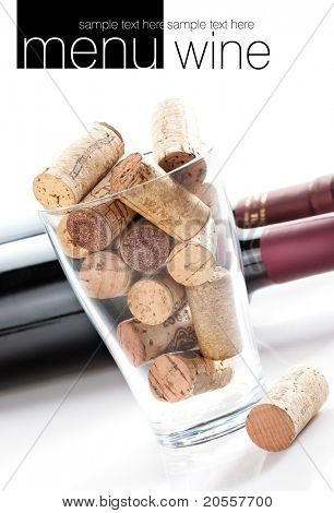 Wine corks in glass jar. Two botles of wine in background. All on white background