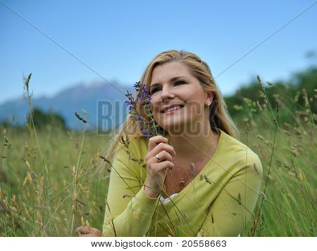 Beautiful Natural Woman With Pure Healthy Skin Outdoors On Spring Field. Switzerland