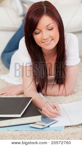 Charming Red-haired Female Studying For While Lying On A Carpet