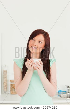 Good Looking Red-haired Woman Enjoying Her Breakfast In The Kitchen