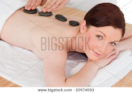 Portrait Of A Serene Red-haired Female Posing While Receiving A Massage