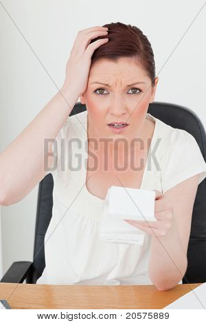 Young Attractive Red-haired Female Being Scared By The Amount Of The Receipt