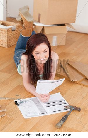 Good Looking Red-haired Girl Reading A Manual Before Do-it-yourself While Lying On The Floor