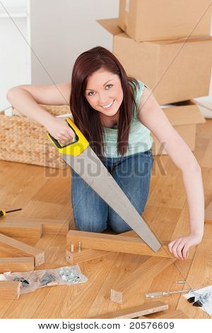 Good Looking Red-haired Woman Using A Saw
