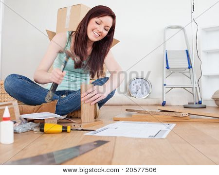 Good Looking Red-haired Female Nailing A Plank At Home