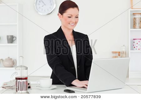 Attractive Red-haired Woman In Suit Relaxing With Her Laptop In The Kitchen