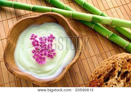 Facial Cream And Flowers In Wood Bowl In A Spa