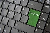 picture of backspace  - A close up to a laptop keyboard which has a green recover key - JPG