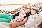 Adorable Baby Girl  Shocked Face, Lying With Her Happy Father And Mother, Young Hipster Couple Relax poster