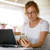 Middle-aged woman using phone and laptop at home  poster