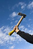 stock photo of infraction law  - hand with an axe on sky background - JPG
