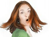 stock photo of brown-haired  - beautiful surprised woman with couloured hair in movement over white - JPG
