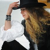 Fashion model portrait with long curly hair, dressed in black leather hat and leather jacket, beaded poster