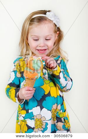 little blond girl looking at ice cream cone.