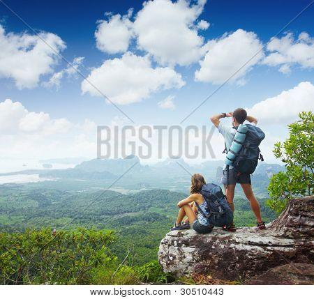 Backpackers on top of a mountain and enjoying valley view