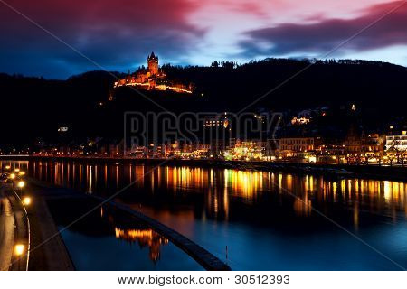 Illuminated City And Castle Close To River