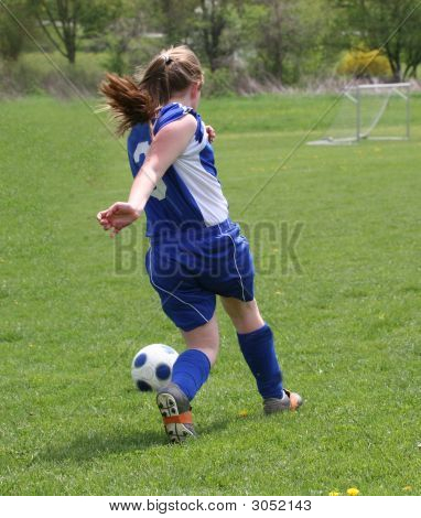 Teen Youth Soccer Player Kicking Ball Down The Field