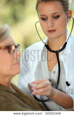 young female doctor auscultating an old woman