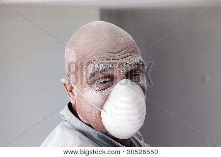 Bald plasterer covered in dust