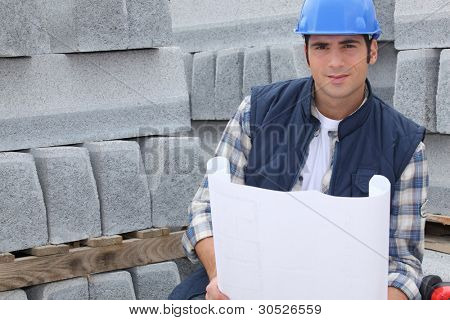 Construction worker standing next to pallets of concrete curb while looking at some plans