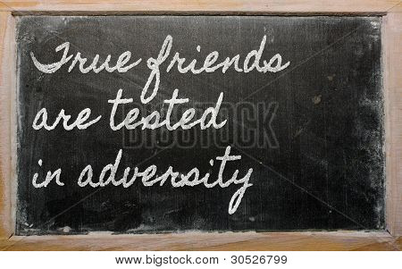 Expression -  True Friends Are Tested In Adversity - Written On A School Blackboard With Chalk