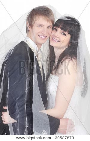 Happy young groom and bride hide under transparent veil isolated on white background