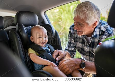 poster of Grandfather tying baby in child seat. Cute little boy going for road trip with grandfather. Happy se