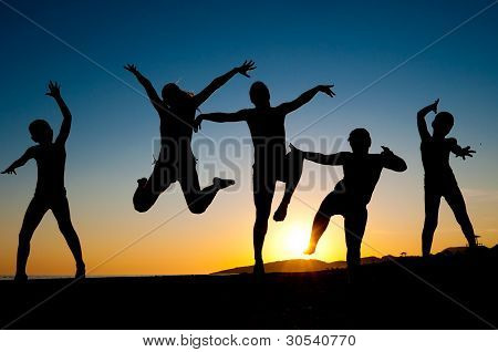 Happy Kids Silhouettes Jumping On The Beach