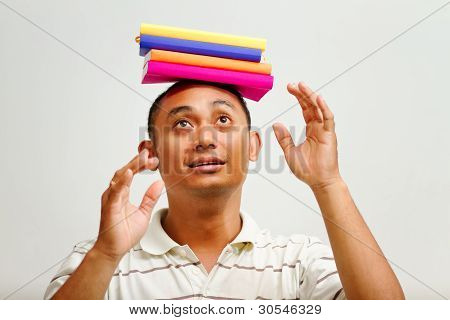 Ethnic Young Man Balancing Books On Head