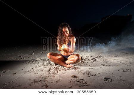 Young Brunette Woman Playing With Sparklers On Beach