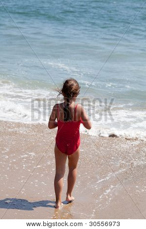 Little Girl Walking Into The Ocean Surf On The Beach