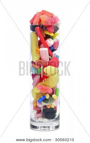 a glass jar full of candies on a white background
