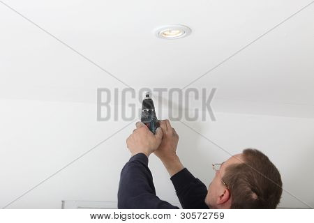 Man Drilling White Ceiling