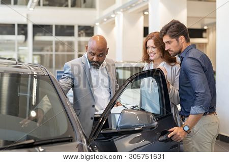 poster of Mature african salesman showing all the car features to young couple. Car dealer showing new car to