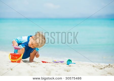 Boy playing with beach toys on tropical beach
