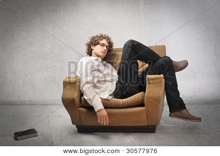 Tired young man lying on an armchair