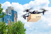 Drone With Cardboard Box Makes Delivery By Air. Drone With Camera Carries Postal Parcel. Background  poster