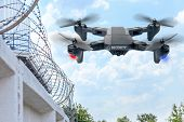 Security Drone Patrols The Territory Across The Sky. Guarding The Wall With Barbed Wire Drone With B poster