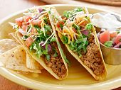 picture of shredded cheese  - Tacos on a platter with tortillas shot with natural light  - JPG