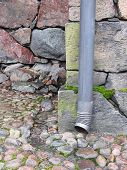 pic of waterspout  - Drainpipe against old stone wall and pavement - JPG