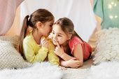 childhood, hygge and friendship concept - happy girls lying in kids tent and gossiping at home poster