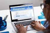 Businesswomans Hand Filing Online Registration Form On Laptop poster