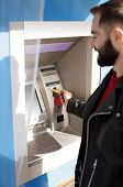 Young Man Inserting Credit Card Into Cash Machine Outdoors poster