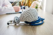 Concept Photo Of Diagnosis And Treatment Of Brain Nervous. In Foreground Is Model Of Brain Near Stet poster