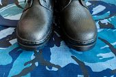 A Pair Of Black Army Boots On Fabric With Blue Camouflage . No People. Army Boots For The Soldier. T poster