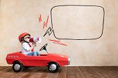 Happy Child Speaking To Megaphone At Home. Funny Kid Driving Toy Car Indoor. Success And Win Concept poster